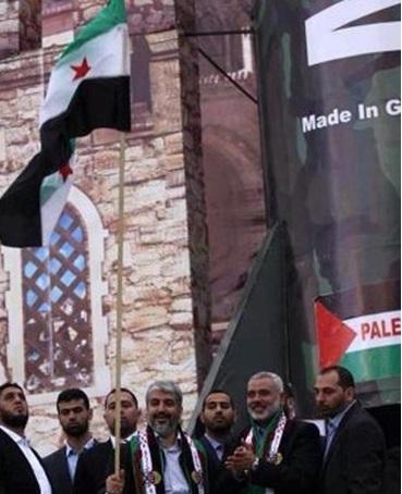 خالد مشعل، حین مراسم استقبال از اوّلین سفر وی به غزّه، پرچم معارضین سوری را به دست گرفت
