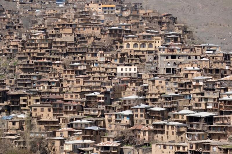 تصویر بالا روستای کنگ در مشهد را نشان می دهد که طی آن میزبان هلنا و دیگر توریست ها، در یکی از تراسهای خود، چایی و هندوانه به میهمانان خود تعارف می کند.