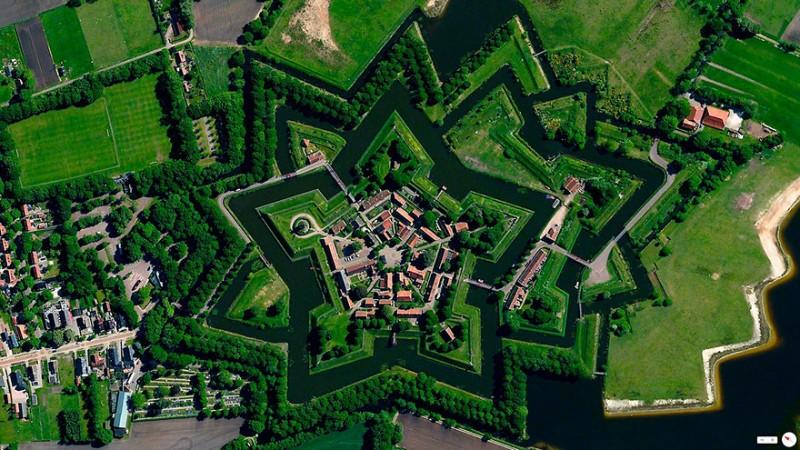 """بورتانگ (Bourtang)، ولاختوده (Vlagtweede)، هلند """"بورتانگ"""" روستایی است با جمعیتی در حدود 430 نفر که در بخش """"ولاختوده"""" در کشور هلند واقع شده است. قلعه و استحکامات نظامی ستاره شکلی که در تصویر مشاهده میکنید در سال 1593 و در طول جنگ هشتاد ساله ساخته شد آن هم زمانی که ویلیام اول قصد داشت تنها جاده بین آلمان و شهر گرونینگن (Groningen) را تحت کنترل داشته باشد. هم اکنون این روستا به عنوان یک موزه فضای باز شناخته میشود."""