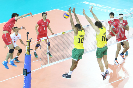 Amir Ghafour (left) of Iran spikes against Lucarelli and Saatkamp (BRA)