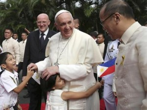 A girl embraces Pope Francis after a welcoming ceremony at the Malacanang Palace in Manila